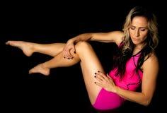 La mujer en pantalones cortos rosados y el tanque sientan el lado con las piernas para arriba miran abajo Fotografía de archivo