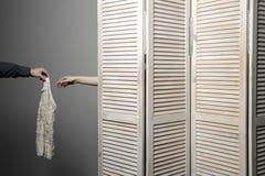 La mujer en parada del vestuario, la mano del hombre somete el vestido imagenes de archivo