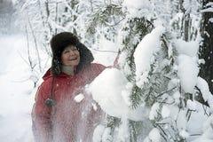 La mujer en parque del invierno despeja nieve de una risa de la rama Imagen de archivo libre de regalías
