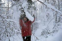 La mujer en parque del invierno despeja nieve de una risa de la rama imagenes de archivo