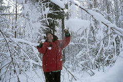La mujer en parque del invierno despeja nieve de una risa de la rama Foto de archivo libre de regalías