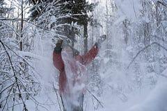 La mujer en parque del invierno despeja nieve de una risa de la rama Fotografía de archivo libre de regalías