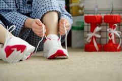 La mujer en pijamas ata los cordones de calzados atléticos Imagen de archivo libre de regalías