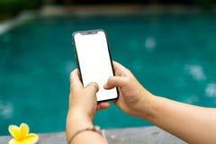 La mujer en la piscina que lleva a cabo ambas manos llama por teléfono con una pantalla y un marco moderno menos diseño foto de archivo libre de regalías