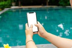 La mujer en la piscina que lleva a cabo ambas manos llama por teléfono con una pantalla y un marco moderno menos diseño fotos de archivo