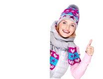 La mujer en prendas de vestir exteriores del invierno sostiene la bandera con los pulgares encima de la muestra Fotos de archivo libres de regalías