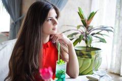 La mujer en restaurante está bebiendo el cóctel Imágenes de archivo libres de regalías