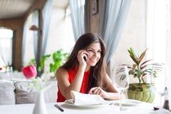 La mujer en restaurante está hablando con el teléfono móvil Fotografía de archivo