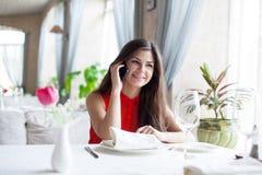 La mujer en restaurante está hablando con el teléfono móvil Foto de archivo libre de regalías