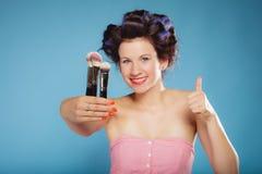 La mujer en rodillos del pelo sostiene cepillos del maquillaje Imagen de archivo libre de regalías