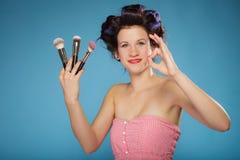 La mujer en rodillos del pelo sostiene cepillos del maquillaje Fotografía de archivo