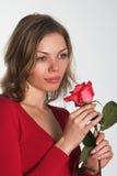 La mujer en rojo con una flor imagen de archivo