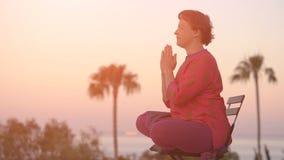 La mujer en ropa étnica practica yoga y medita en la posición de loto almacen de metraje de vídeo