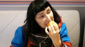 La mujer en ropa brillante come la pizza y el café de las bebidas almacen de video