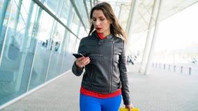 La mujer en ropa brillante está rodando la maleta amarilla cerca del aeropuerto almacen de video