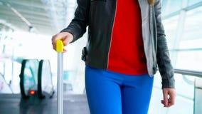La mujer en ropa brillante está rodando la maleta amarilla en el aeropuerto metrajes