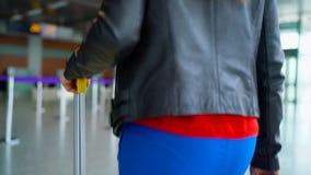 La mujer en ropa brillante está rodando la maleta amarilla en el aeropuerto almacen de video
