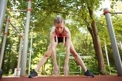 La mujer en la ropa de deportes que hace ejercicio arquea en la naturaleza del verano Fotografía de archivo libre de regalías