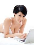 La mujer en ropa interior está trabajando en la computadora portátil fina Imagen de archivo