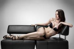 La mujer en ropa interior miente en el sofá Fotos de archivo