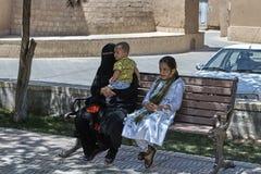 La mujer en ropa islámica se sienta en banco con dos niños Fotos de archivo