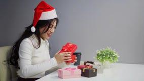La mujer en santa tenía caja de regalo de la Navidad de la abertura