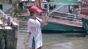 La mujer en la sari blanca tira los barcos locales en el teléfono en bahía almacen de video