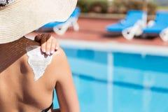La mujer en sombrero est? aplicando la crema del sol en su hombro por la piscina Factor de protecci?n de Sun en las vacaciones, c imagenes de archivo