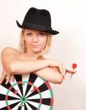 La mujer en sombrero lleva a cabo a la tarjeta para los dardos en blanco Foto de archivo libre de regalías