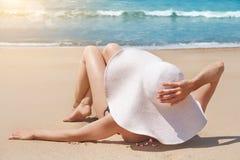 La mujer en sombrero miente en la arena blanca en la playa fotografía de archivo libre de regalías