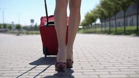 La mujer en sombrero rojo camina con la maleta roja afuera almacen de metraje de vídeo
