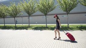 La mujer en sombrero rojo camina con la maleta roja afuera metrajes