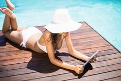 La mujer en sombrero y el bikini usando la tableta digital en apilador de madera por la piscina echan a un lado Imagenes de archivo