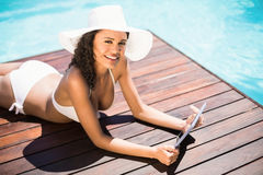 La mujer en sombrero y el bikini usando la tableta digital en apilador de madera por la piscina echan a un lado Fotografía de archivo libre de regalías