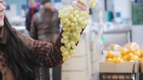 La mujer en supermercado selecciona las uvas metrajes