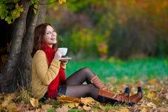 La mujer en suéter beige y la bufanda roja beben té Fotografía de archivo