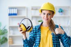 La mujer en taller con los auriculares de la cancelación de ruido fotos de archivo libres de regalías