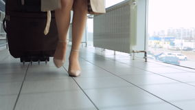 La mujer en talones va en la maleta del aeropuerto y del rollo en las ruedas metrajes