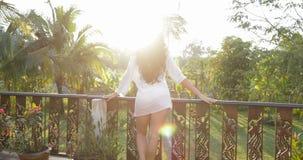 La mujer en terraza del verano disfruta de la opinión Forest At Sunset Back Rear tropical de la muchacha morena atractiva al aire metrajes