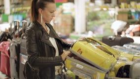 La mujer en la tienda elige la maleta para el viaje de las vacaciones La mujer abre la maleta y ve en el pasillo de almacen de metraje de vídeo
