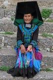 La mujer en traje colorido brillante se está sentando en Imagenes de archivo