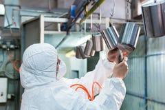 La mujer en traje protector sopla el aire en las piezas de metal antes de la pintura del polvo foto de archivo libre de regalías