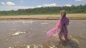 La mujer en un boho de seda camina en el agua