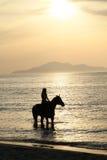 La mujer en un caballo y una puesta del sol del oro Fotos de archivo libres de regalías