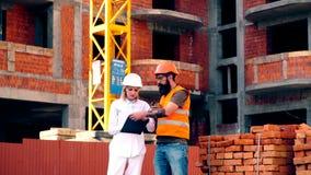 La mujer en un casco y una carpeta comunica con un hombre barbudo en un chaleco protector contra el contexto de la construcción metrajes