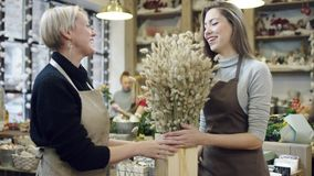La mujer en un delantal da un florero con trigo a una muchacha en un delantal almacen de video