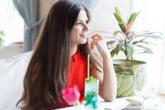 La mujer en un restaurante está bebiendo el cóctel Fotografía de archivo libre de regalías