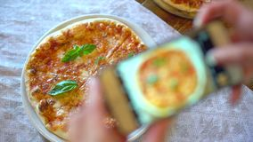 La mujer en un restaurante hace la foto de la comida, pizza con la cámara del teléfono móvil Manos de femenino haciendo una foto  almacen de metraje de vídeo