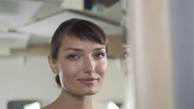 La mujer en un salón de belleza mira su reflexión en el espejo con las lámparas y comprueba ascendente cercano del peinado y del  metrajes