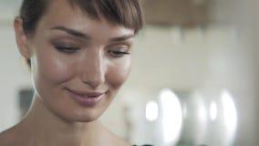 La mujer en un salón de belleza mira su reflexión en el espejo con las lámparas y comprueba ascendente cercano del peinado y del  almacen de video